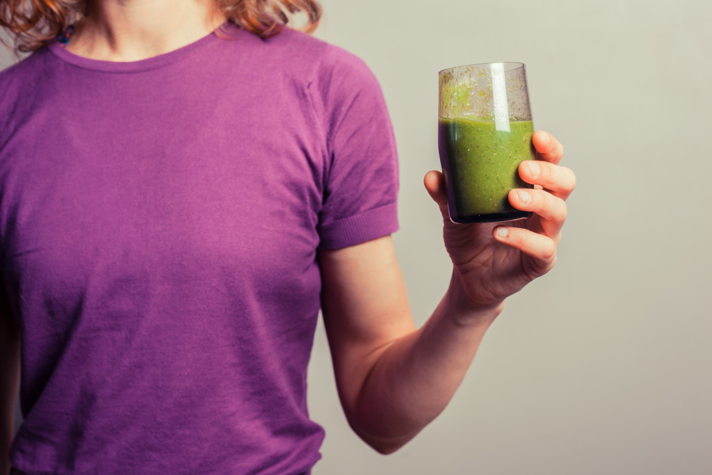 Young Woman Holding A Glass Of Green Smoothie